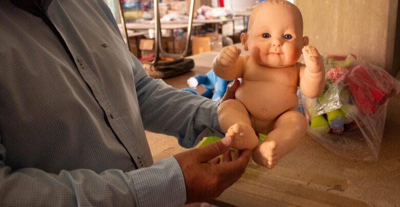 El Sr. Francisco sostiene un muñeco de los que produce en su fábrica, al que solo le faltaba el vestuario para ser terminado.