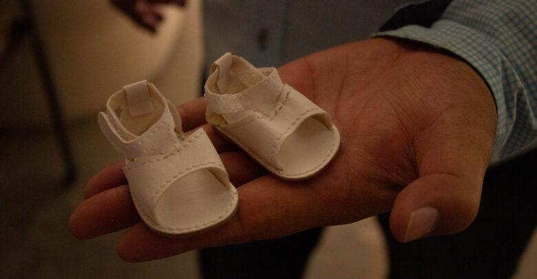 El Sr. Francisco sostiene un par de zapatos de muñeca, un accesorio importante en el juguete.